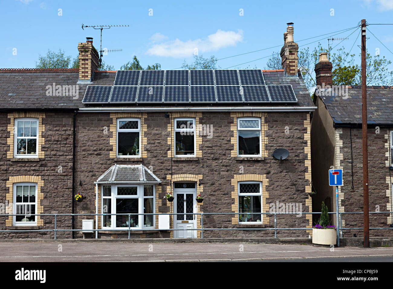 Old stone house in terrace with modern solar panels on roof, Llanfoist, Wales, UK - Stock Image