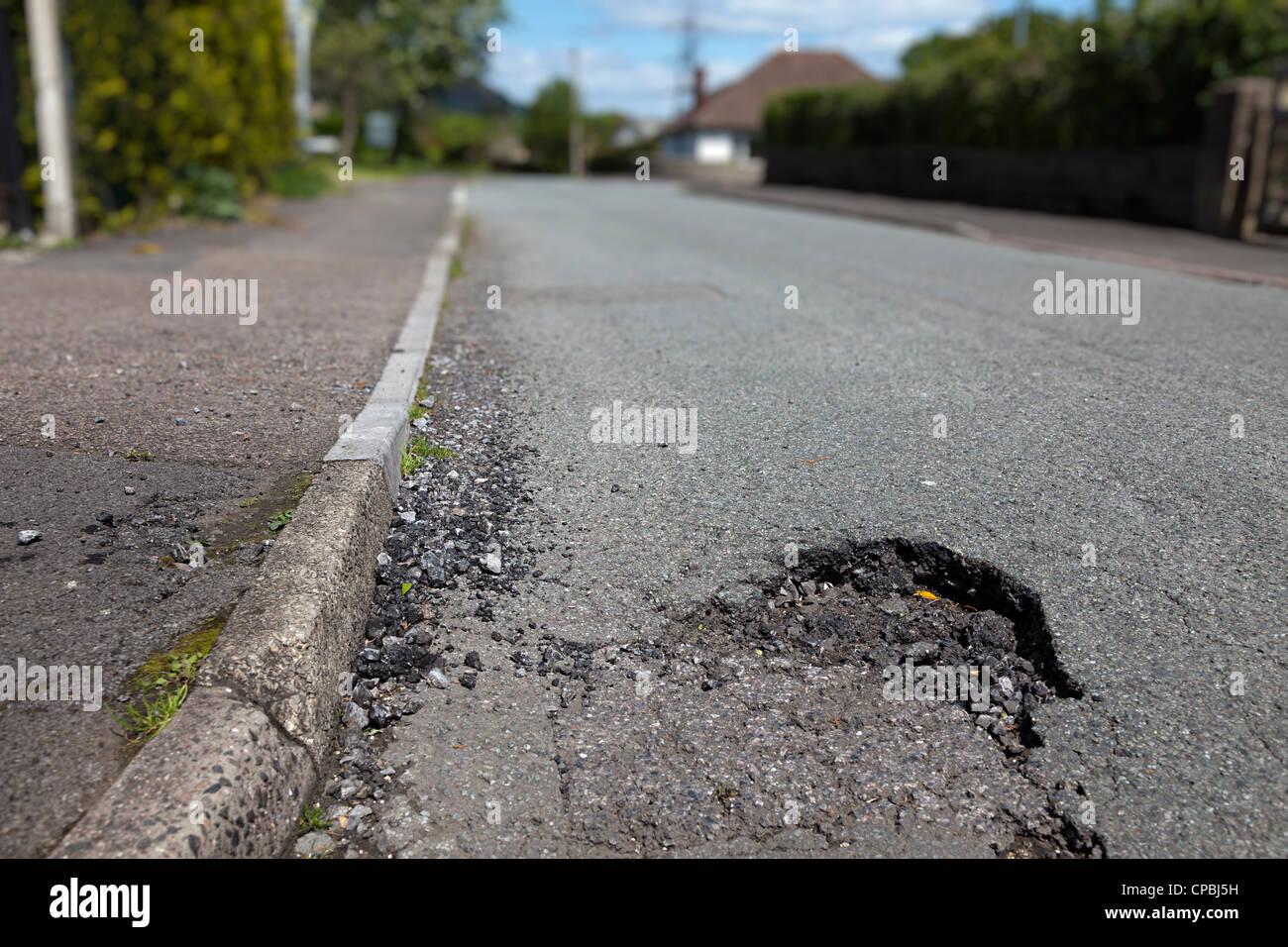 Pothole in road requiring repair, Llanfoist village, Wales, UK - Stock Image