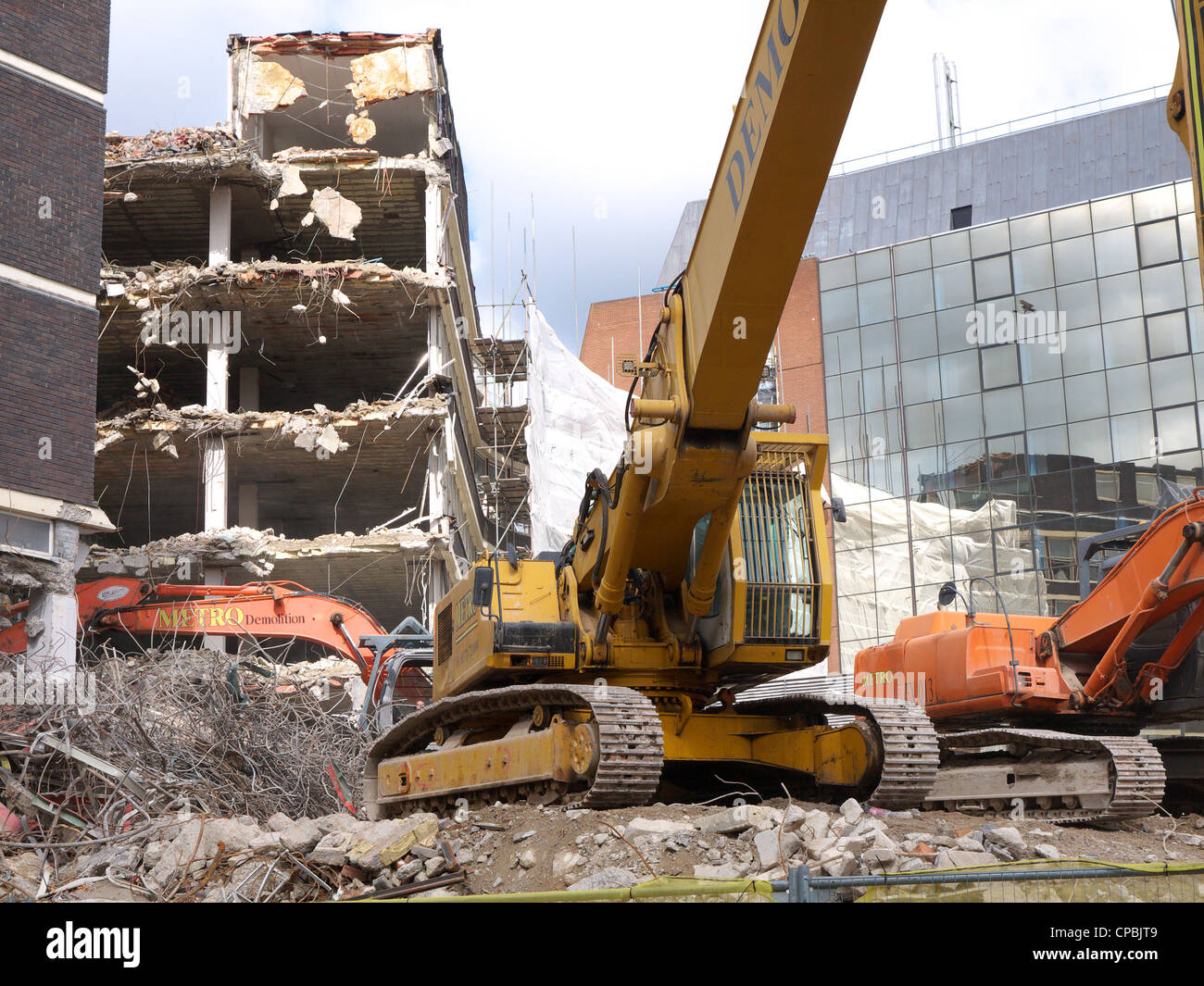 An old building being demolished by heavy machinery - Stock Image