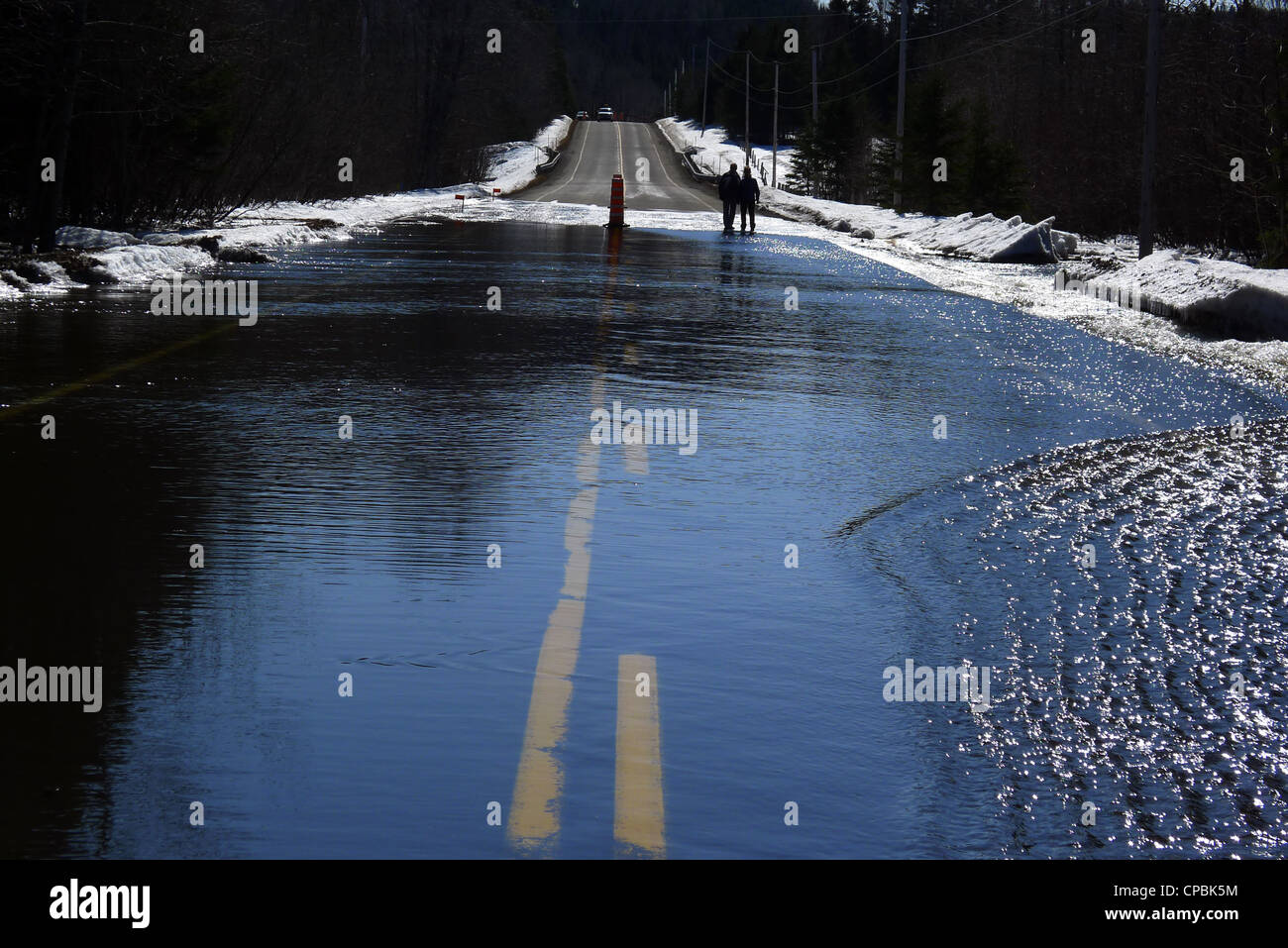 A couple looking at a road blocked by floodwater - Stock Image