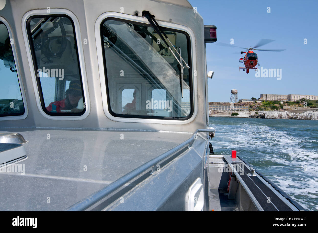 A United States Coast Guard HH-65C Dolphin helicopter approaches a Coast Guard Auxiliary vessel. - Stock Image