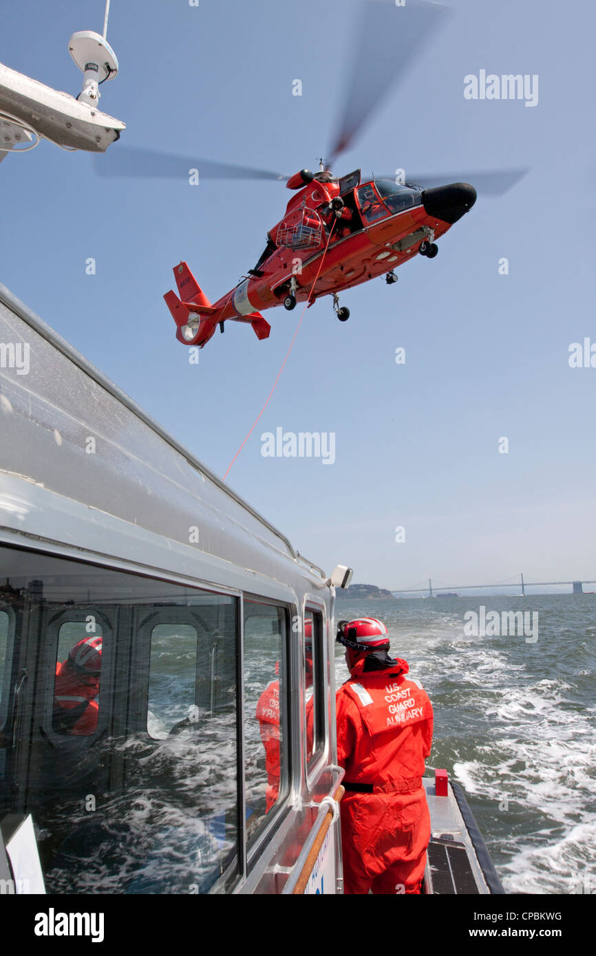A United States Coast Guard HH-65C Dolphin helicopter lowers a rescue basket to the deck of a Coast Guard Auxiliary - Stock Image