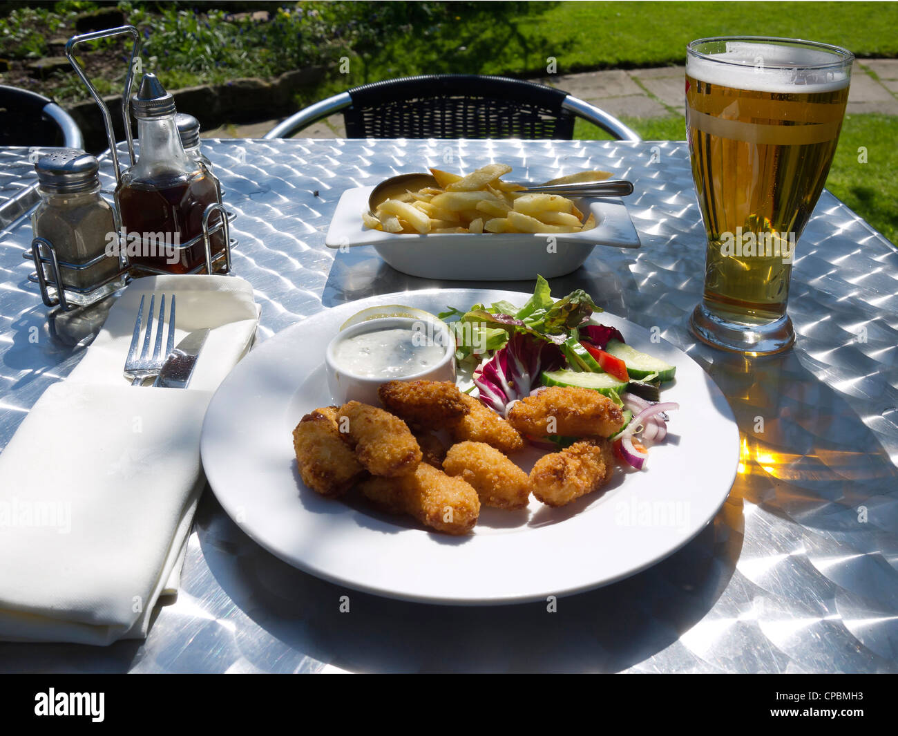Lunch in a pub garden Scampi chips salad and a pint of Lager spring sunshine - Stock Image
