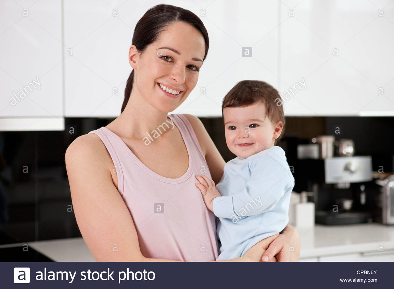 A young mother standing in a kitchen holding her baby son - Stock Image