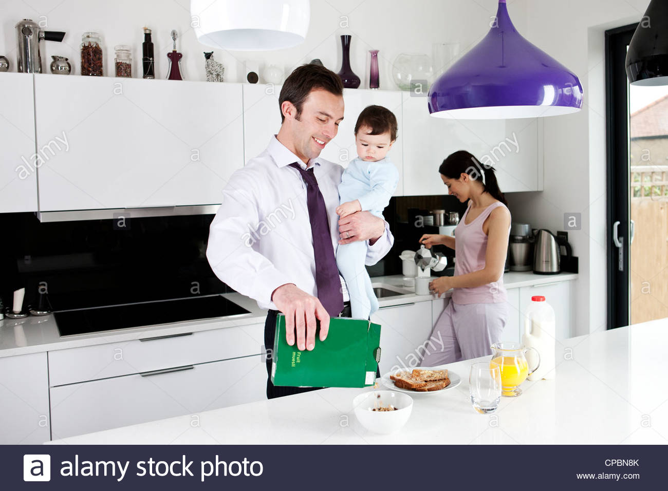 A father holding his baby son whilst making breakfast - Stock Image