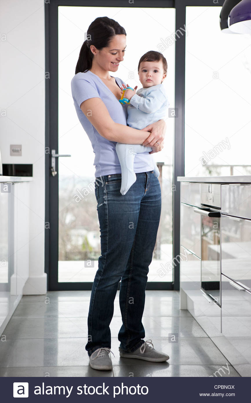 A mother standing in a kitchen holding her baby son - Stock Image