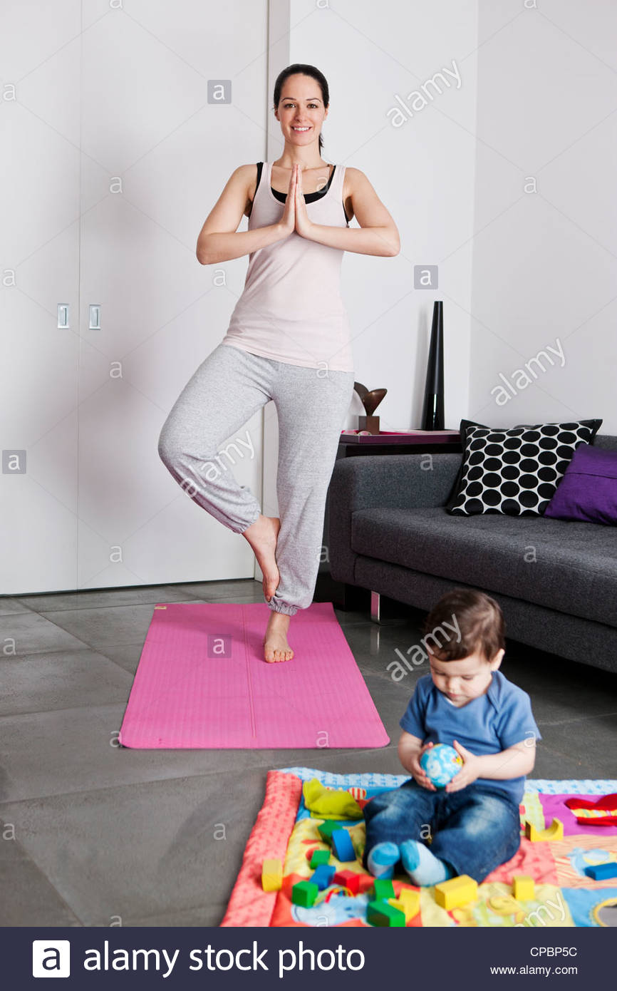 A young mother practicing yoga at home whilst her baby son plays on the floor - Stock Image