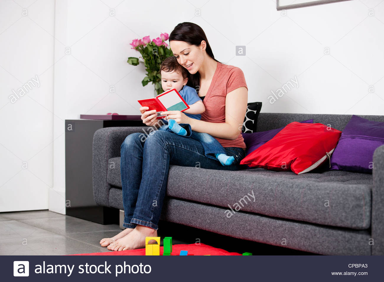 A mother and her baby son sitting on the sofa, reading a book Stock Photo