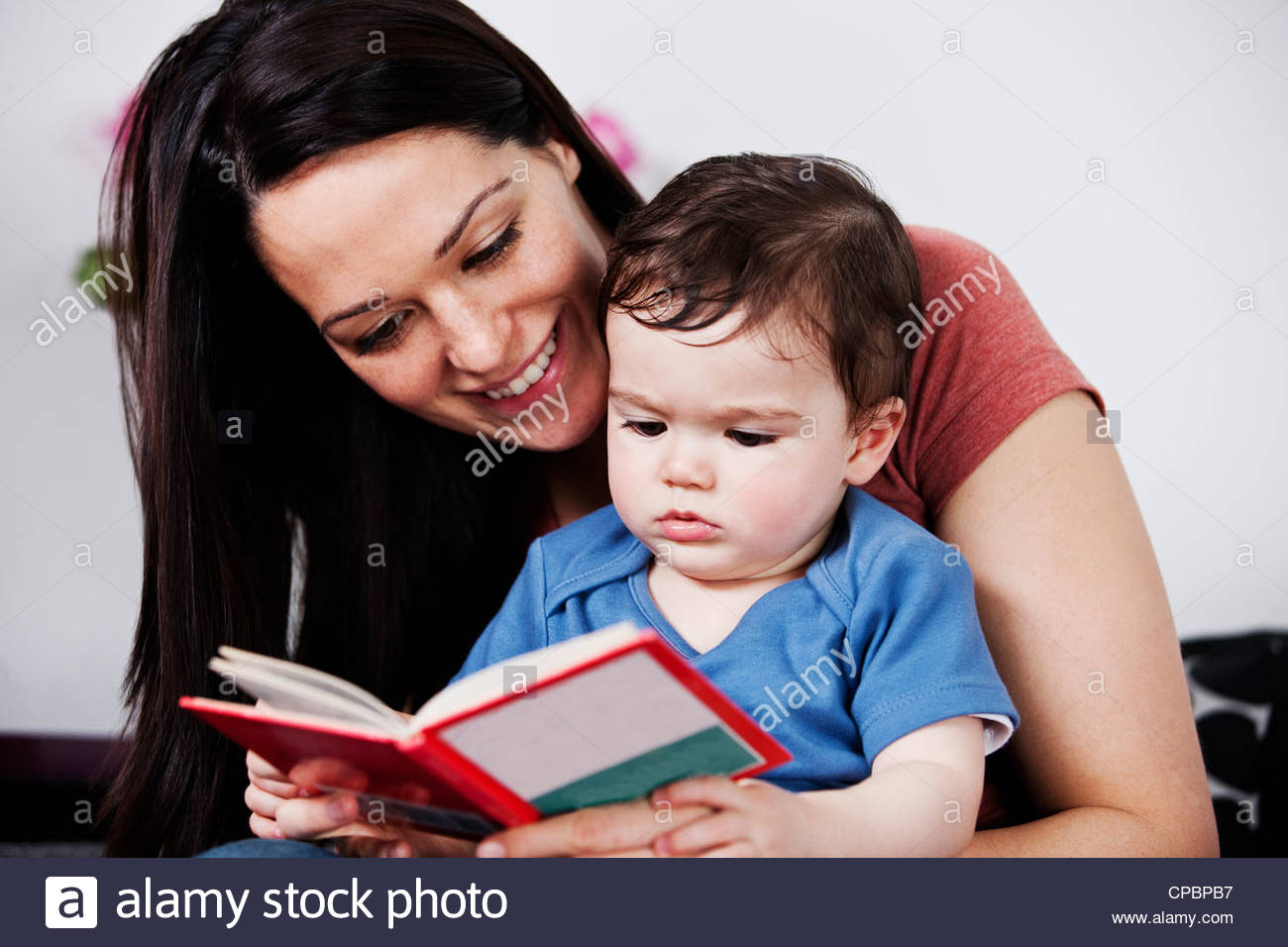 A mother and her baby son reading a book - Stock Image