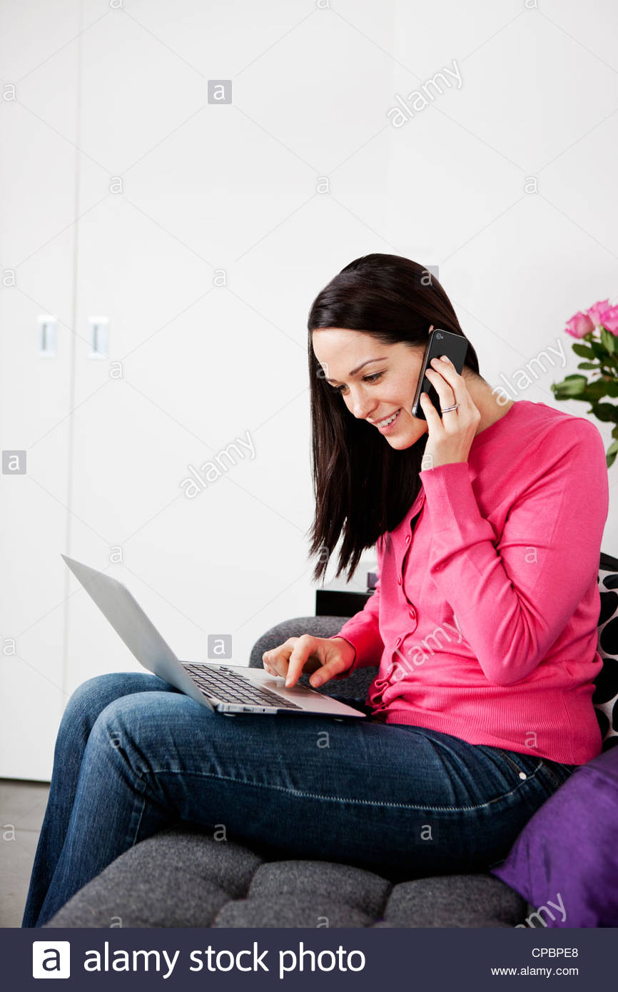 A woman using a laptop and talking on a mobile phone at home - Stock Image