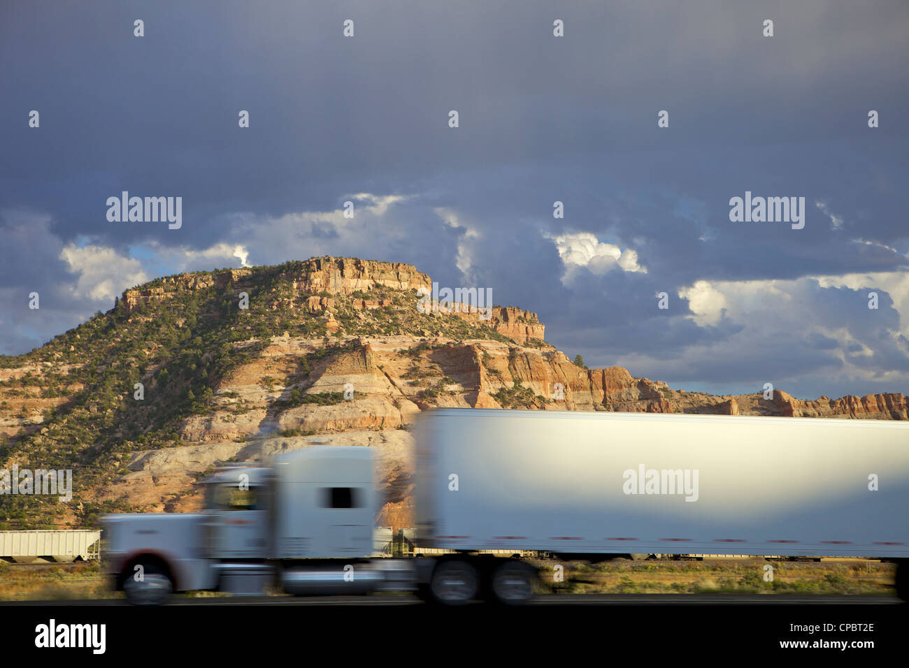 White truck passing rock formation, USA - Stock Image