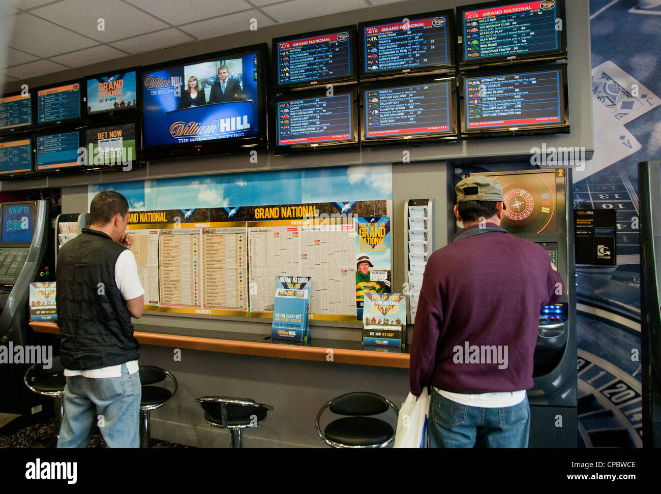 People in betting shop placing bets during grand national horse race Stock Photo
