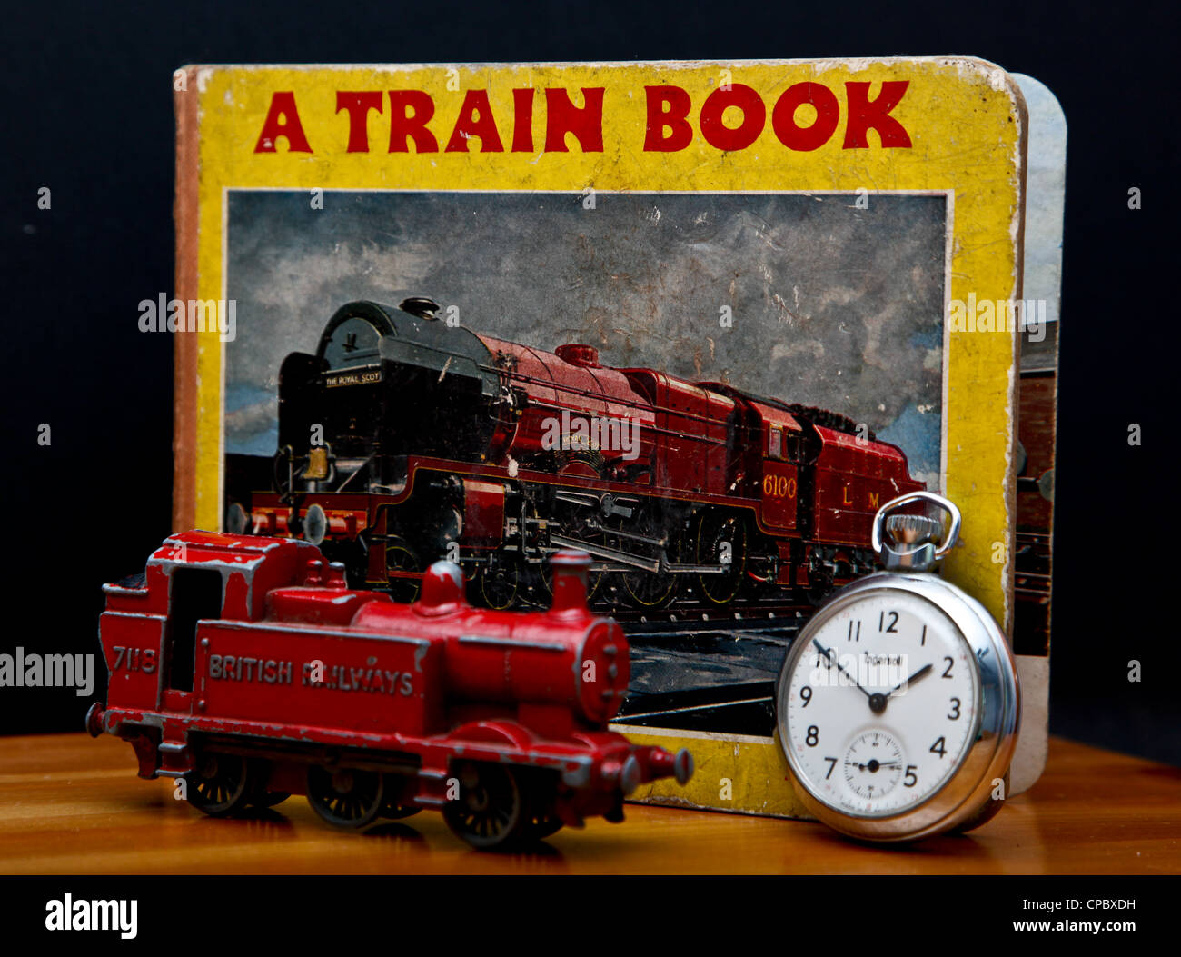 An old child's book about trains with a toy train and pocket watch in front of it. Concept of trains running on Stock Photo