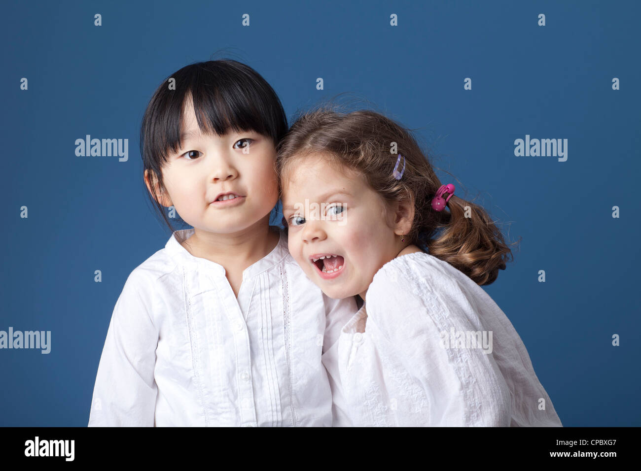Two little girls shot in the studio against a blue background. - Stock Image