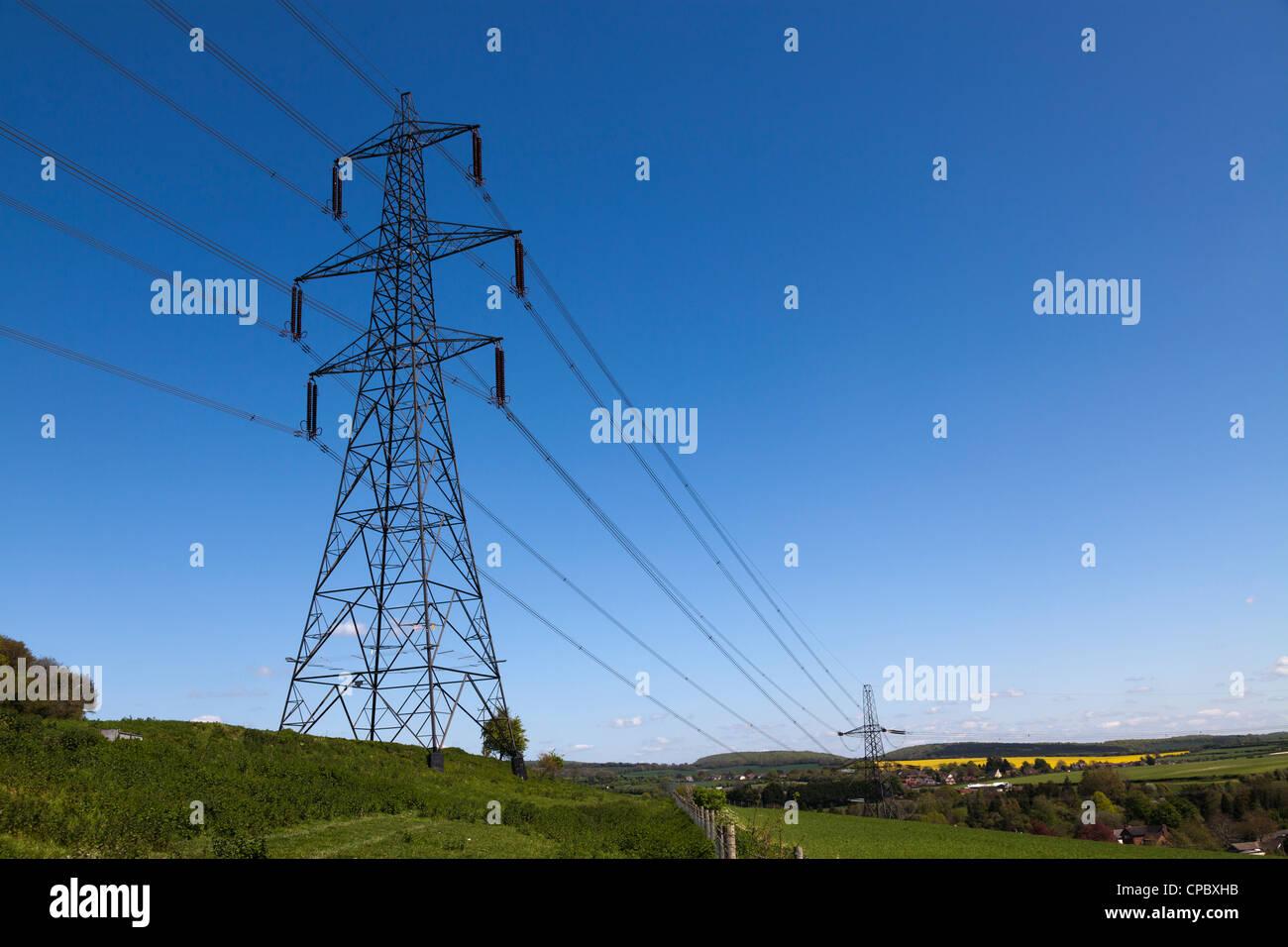 Electricity pylon against deep blue sky - Stock Image