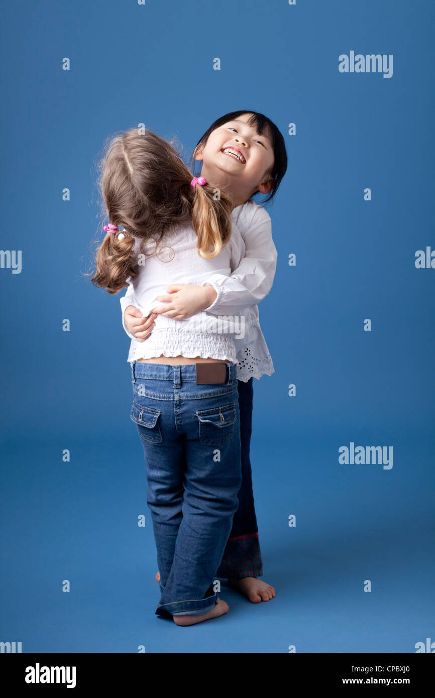 Two little girls hugging and laughing. Shot in the studio against a blue background. - Stock Image