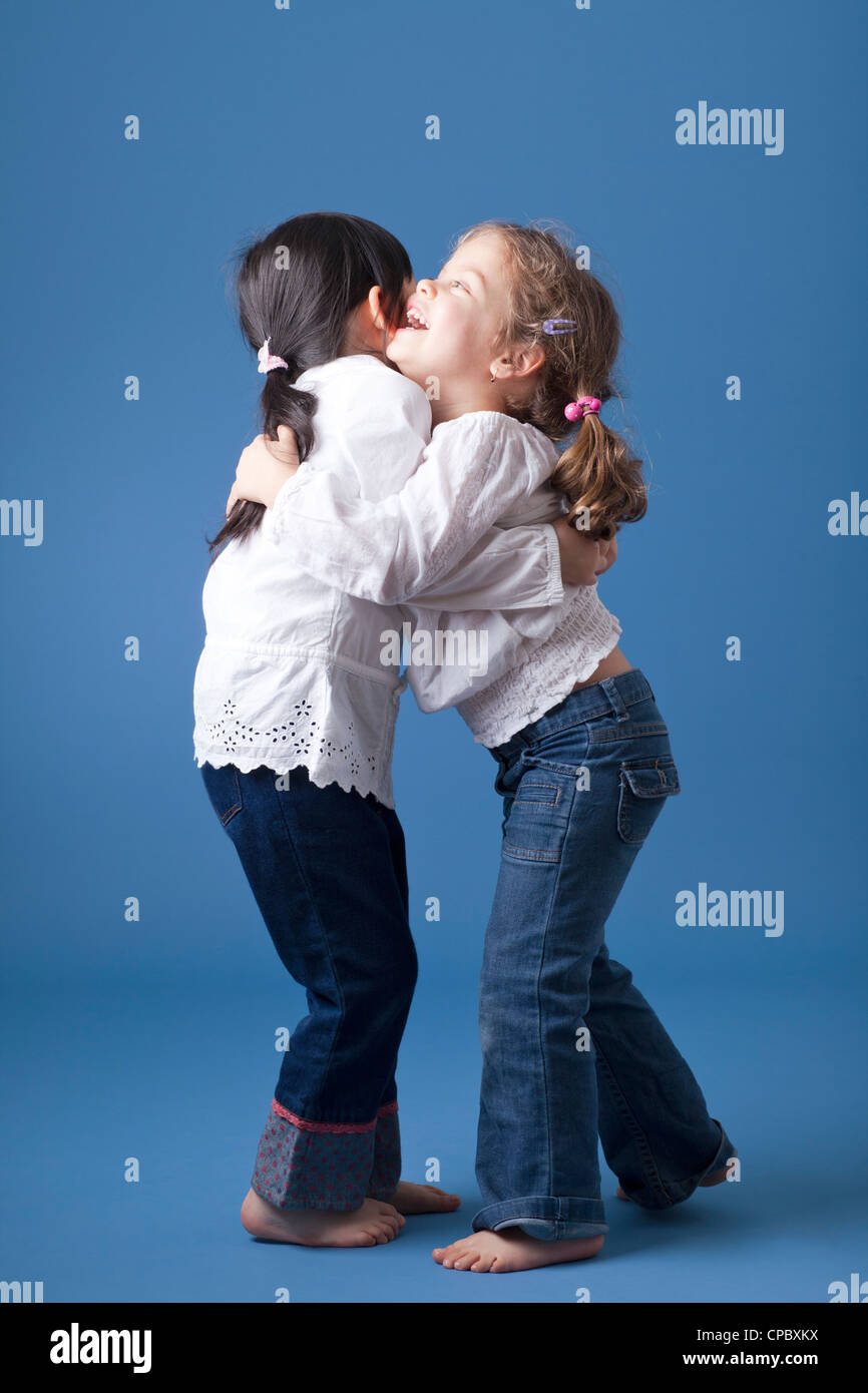 Two little girls hugging. Shot in the studio against a blue background. - Stock Image
