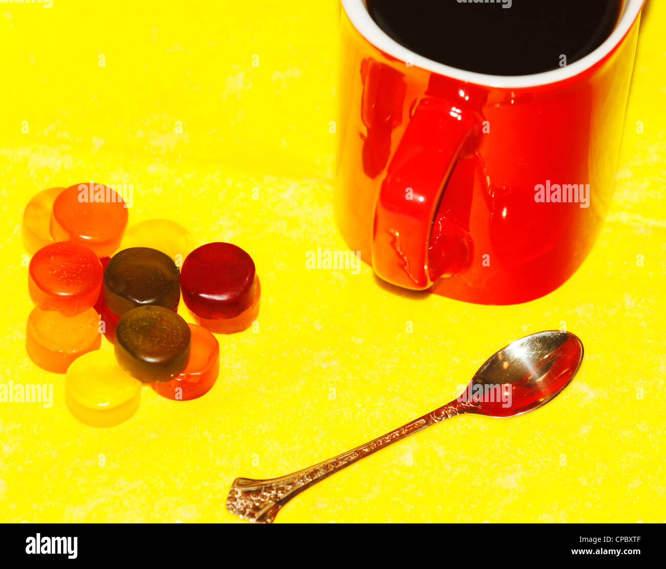 cup of coffee in the red, tasty, pretty sweet, golden spoon on a yellow background - Stock Image