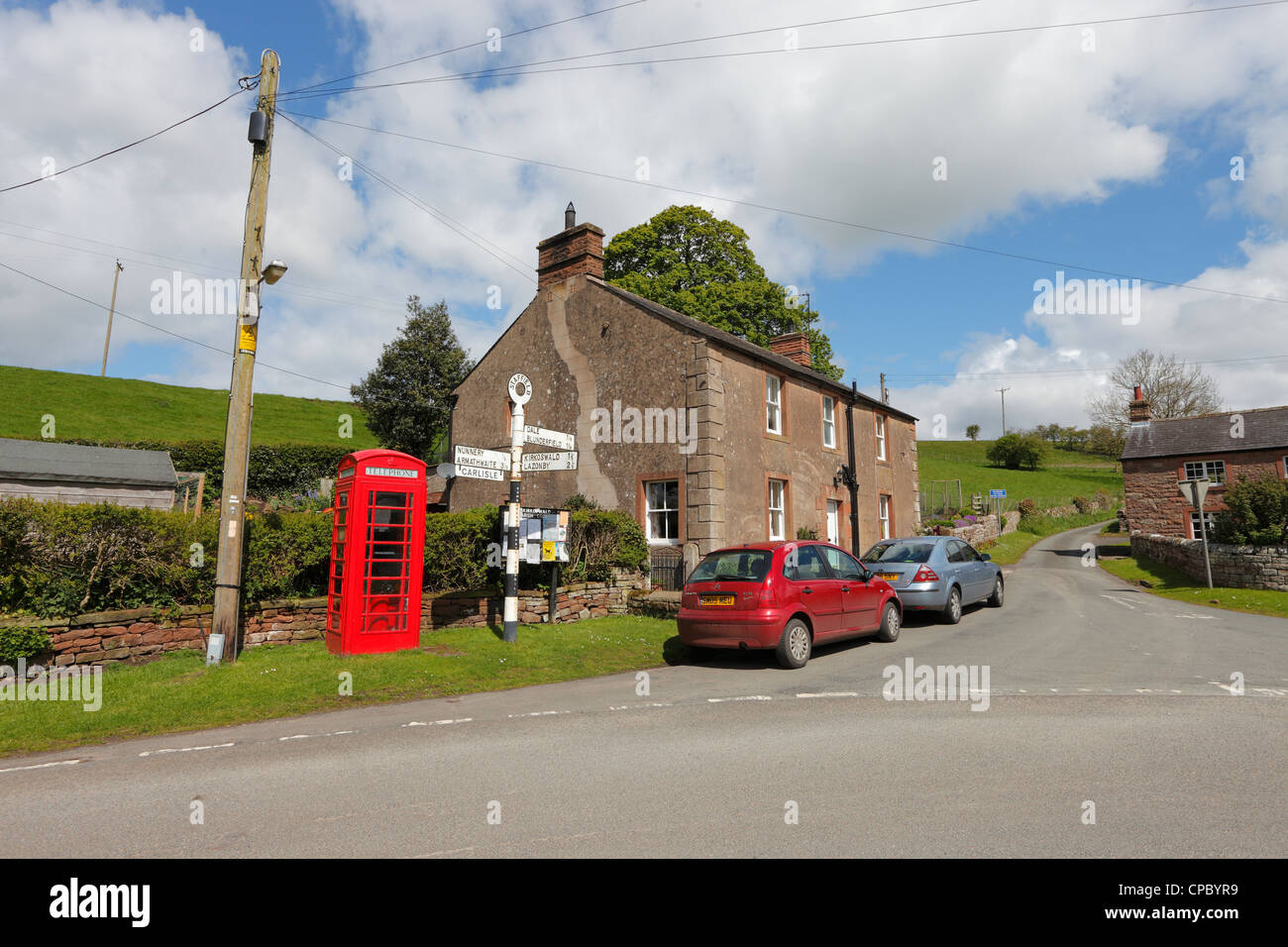 Red telephone box, telegraph pole and sign post in Staffield in the Eden Valley, near Penrith, Cumbria - Stock Image