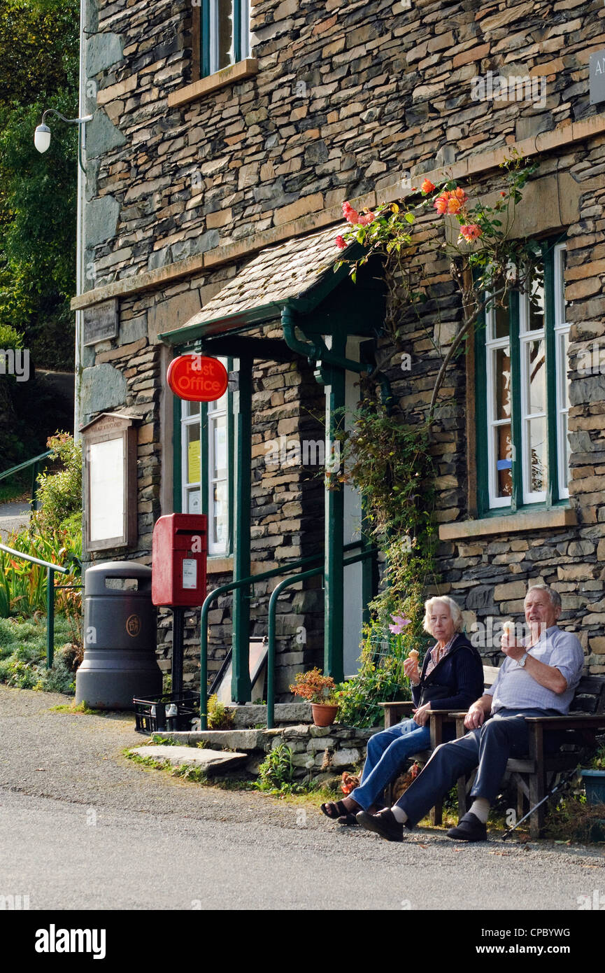 Walkers enjoying an ice-cream outside Troutbeck Post Office, Lake District - Stock Image
