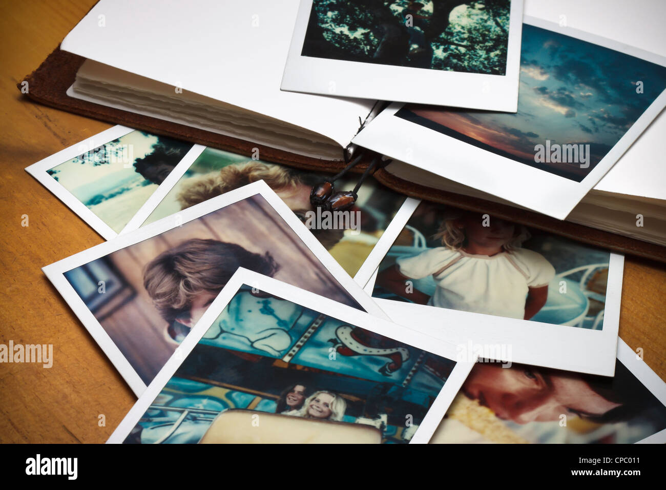 A pile of old pictures and a journal to document memories of past times. - Stock Image