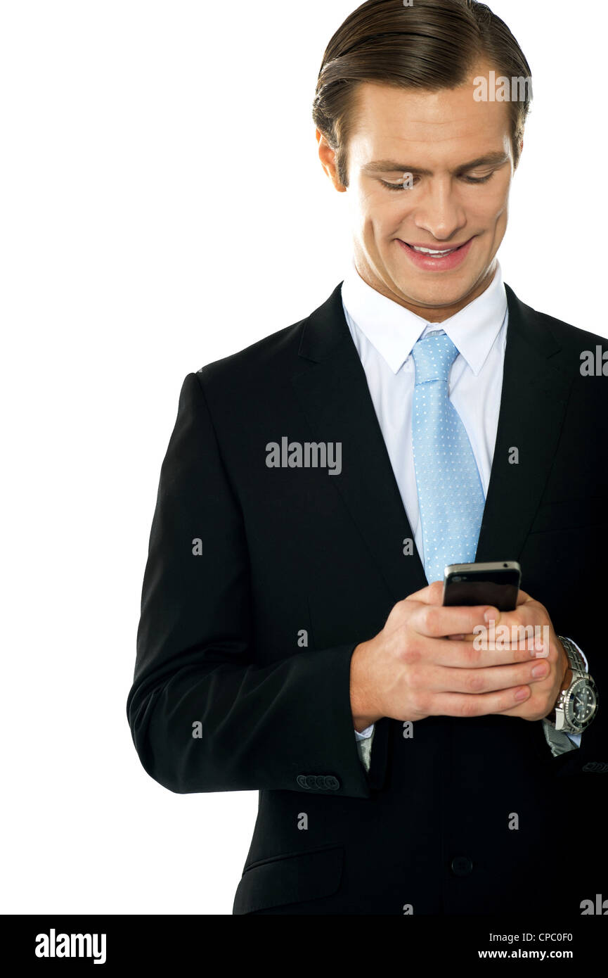 Confident businessperson messaging and smiling - Stock Image