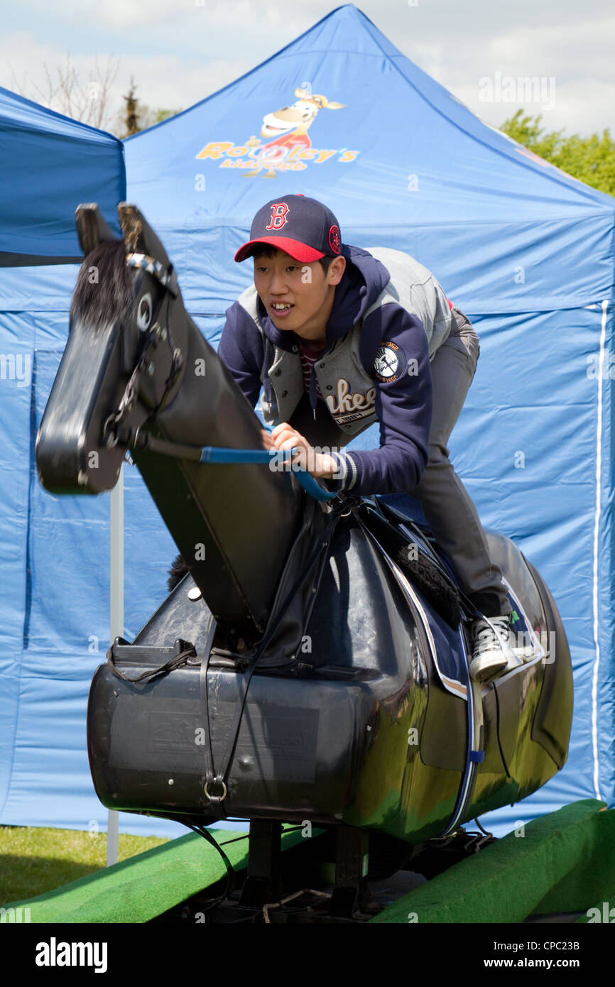 Young Chinese man riding a training horse model, Newmarket festival of Sports, Suffolk East Anglia UK - Stock Image