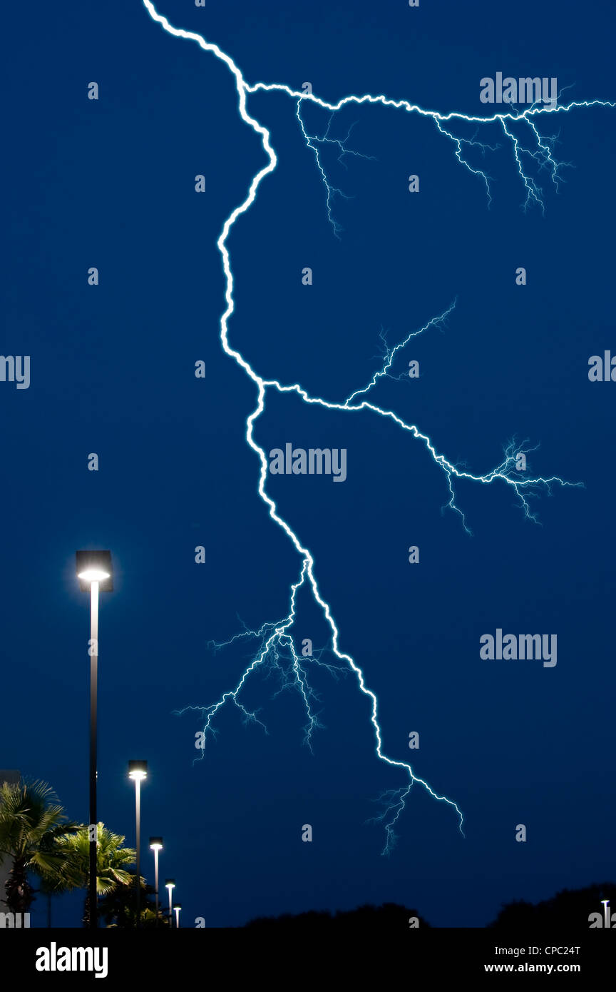 lightning bolt in night sky over street lights - Stock Image