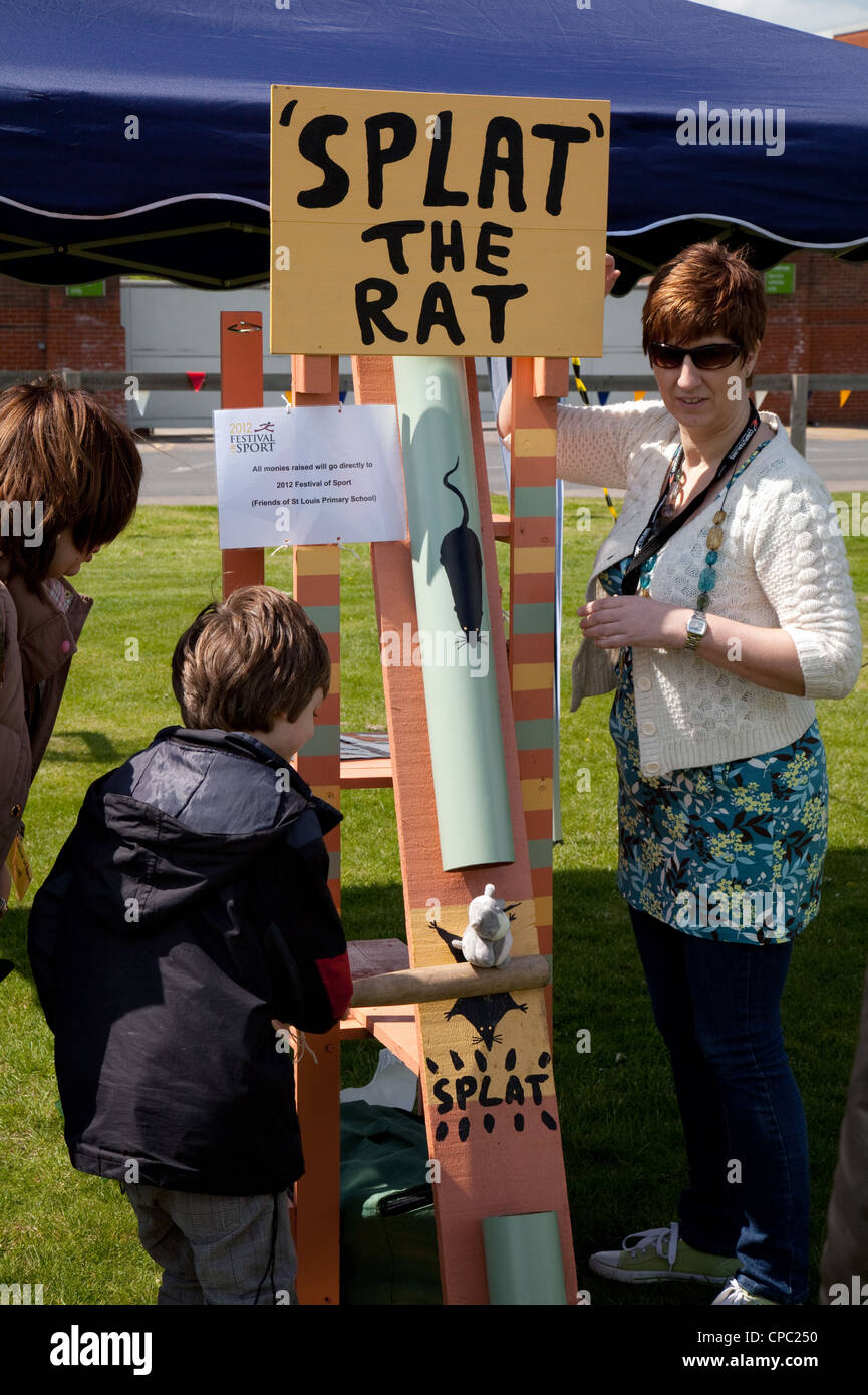 Child playing on the 'Splat the rat' game, Newmarket town fair, Suffolk UK - Stock Image