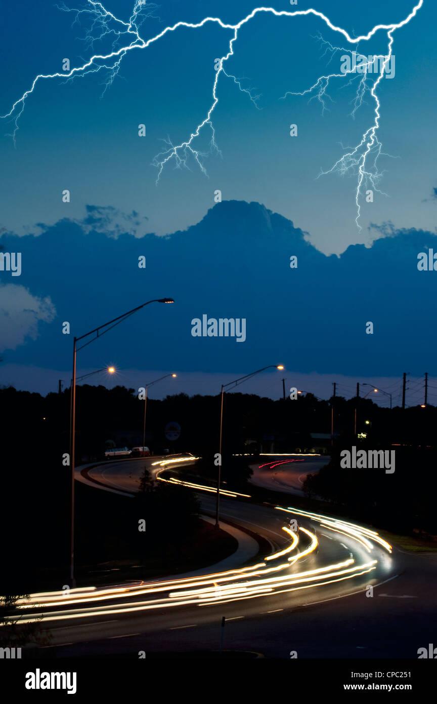 lightning bolt in night sky over highway - Stock Image