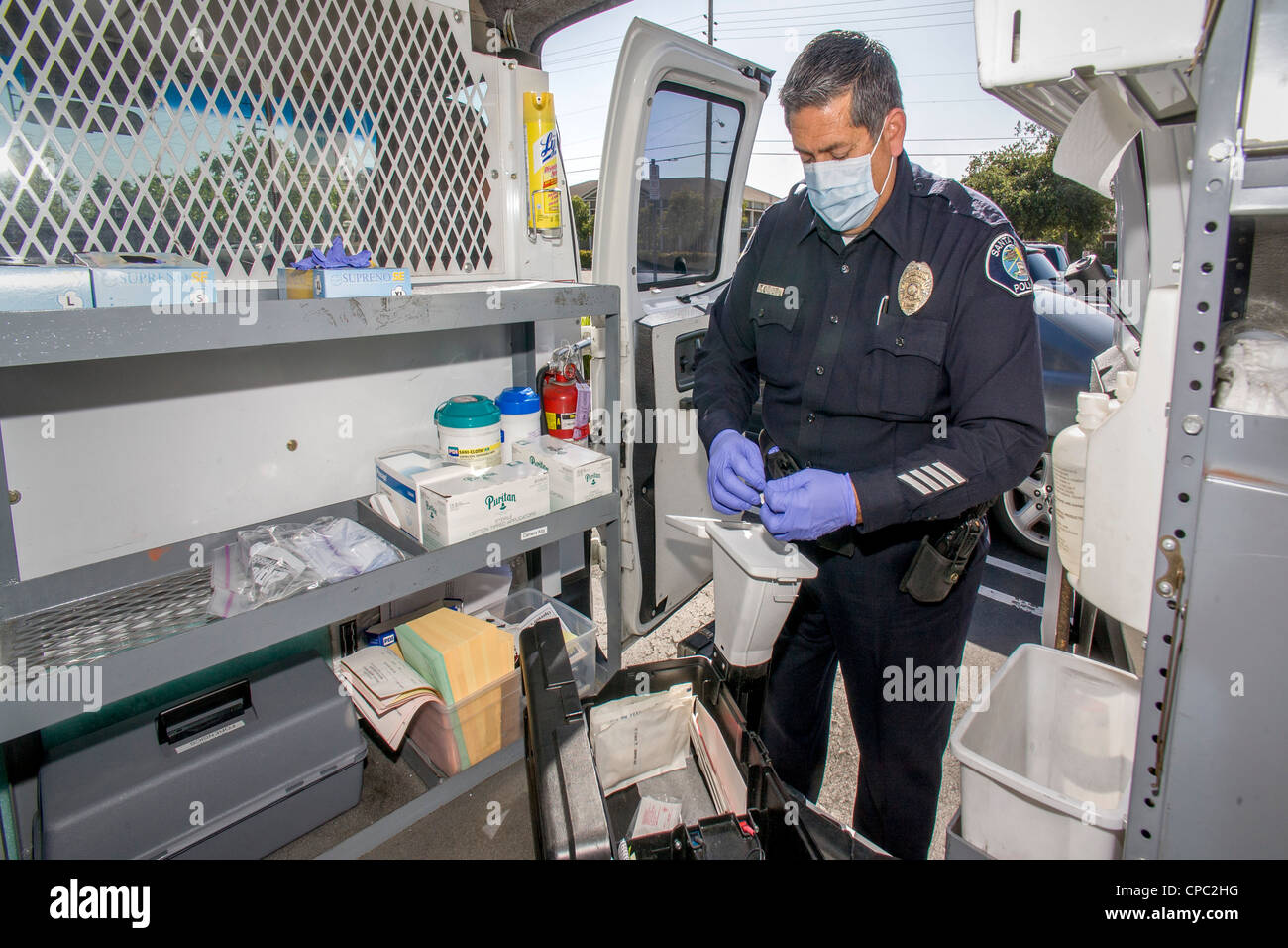 In his official van in Santa Ana, CA, a Hispanic police officer prepares a scent transfer unit at a crime scene. - Stock Image