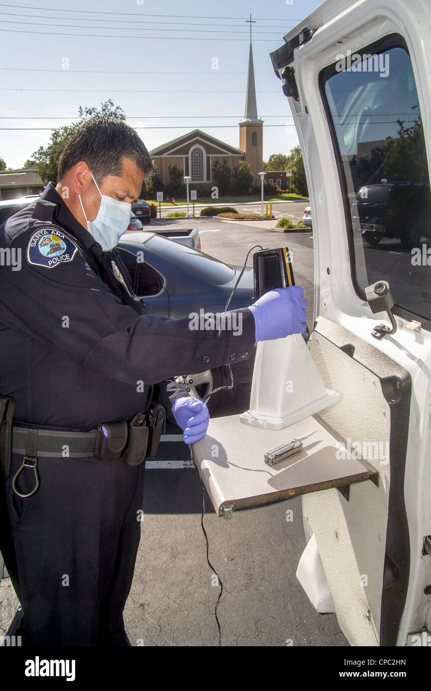 At  his official van Hispanic police officer uses a scent transfer unit to examine a knife at a crime scene. - Stock Image