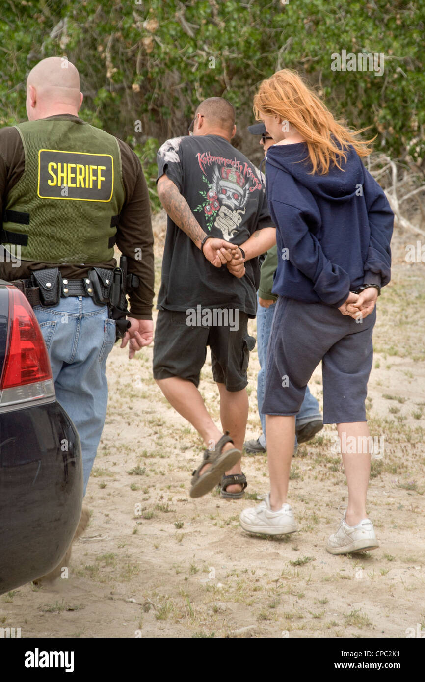 Sheriff's deputies arrest a homeless woman on an outstanding warrant in Victorville, CA, during the search of - Stock Image