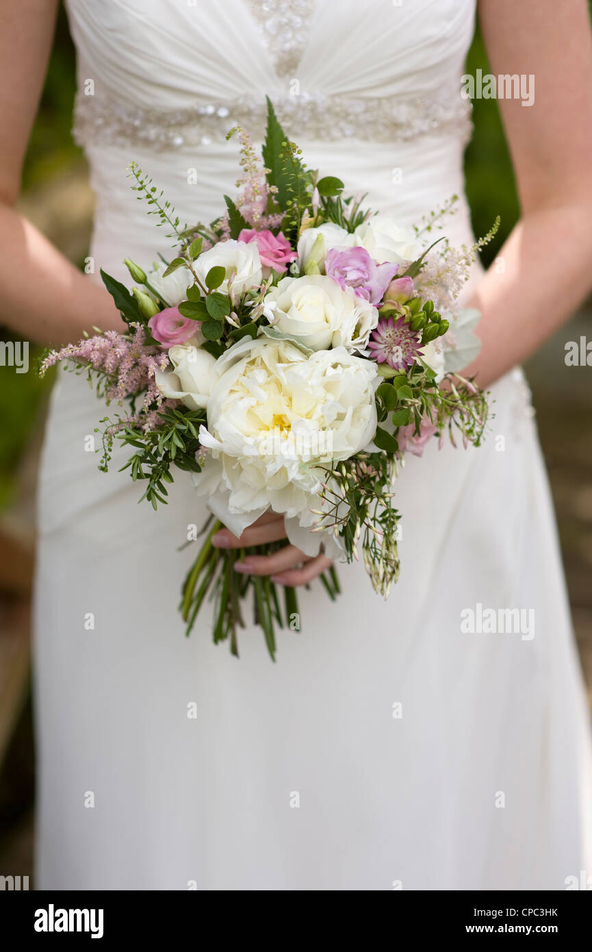 bride holds a bouquet of wedding flowers - Stock Image
