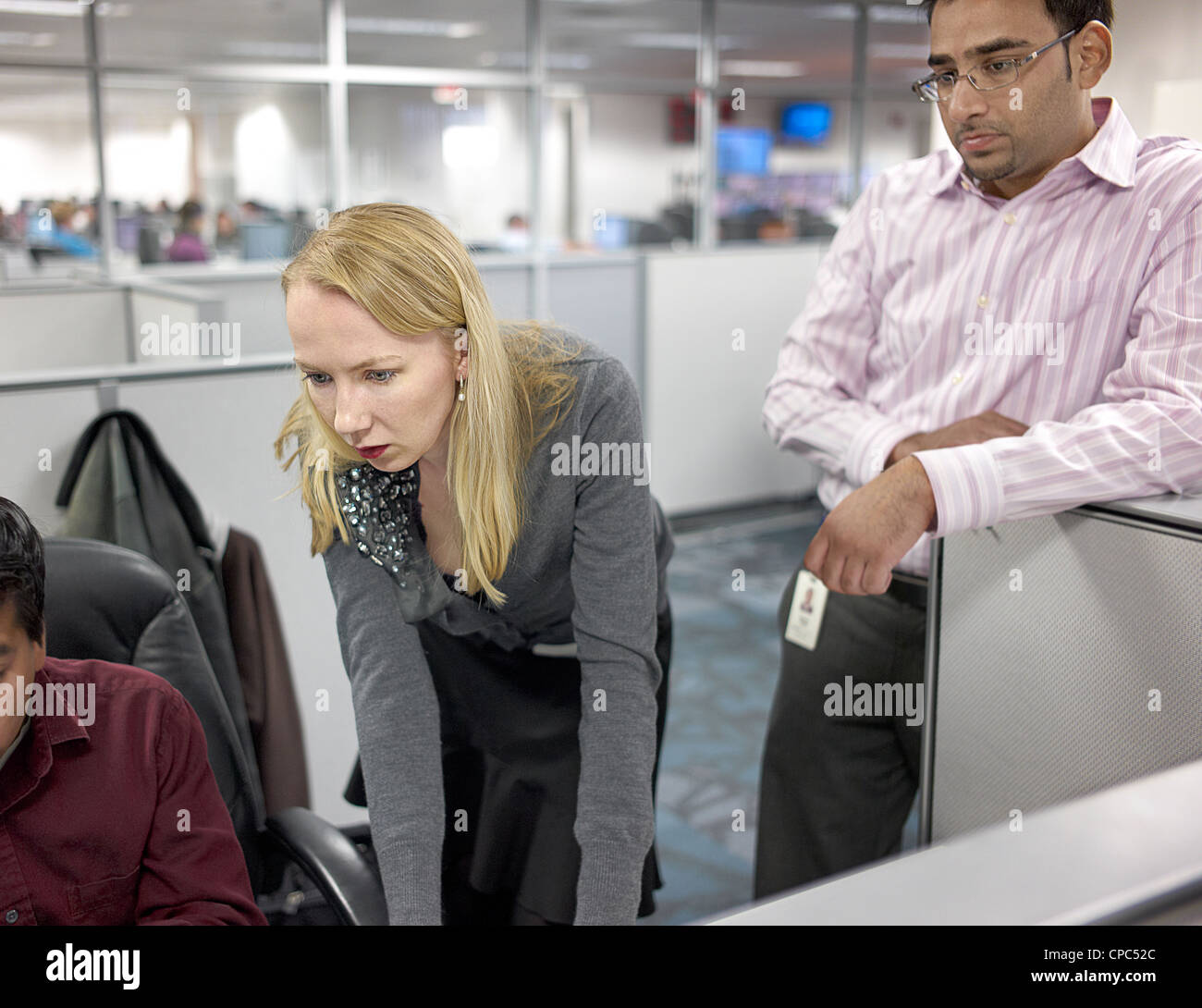 Two workers looking over the shoulder of their coworkers in a cubicle. - Stock Image