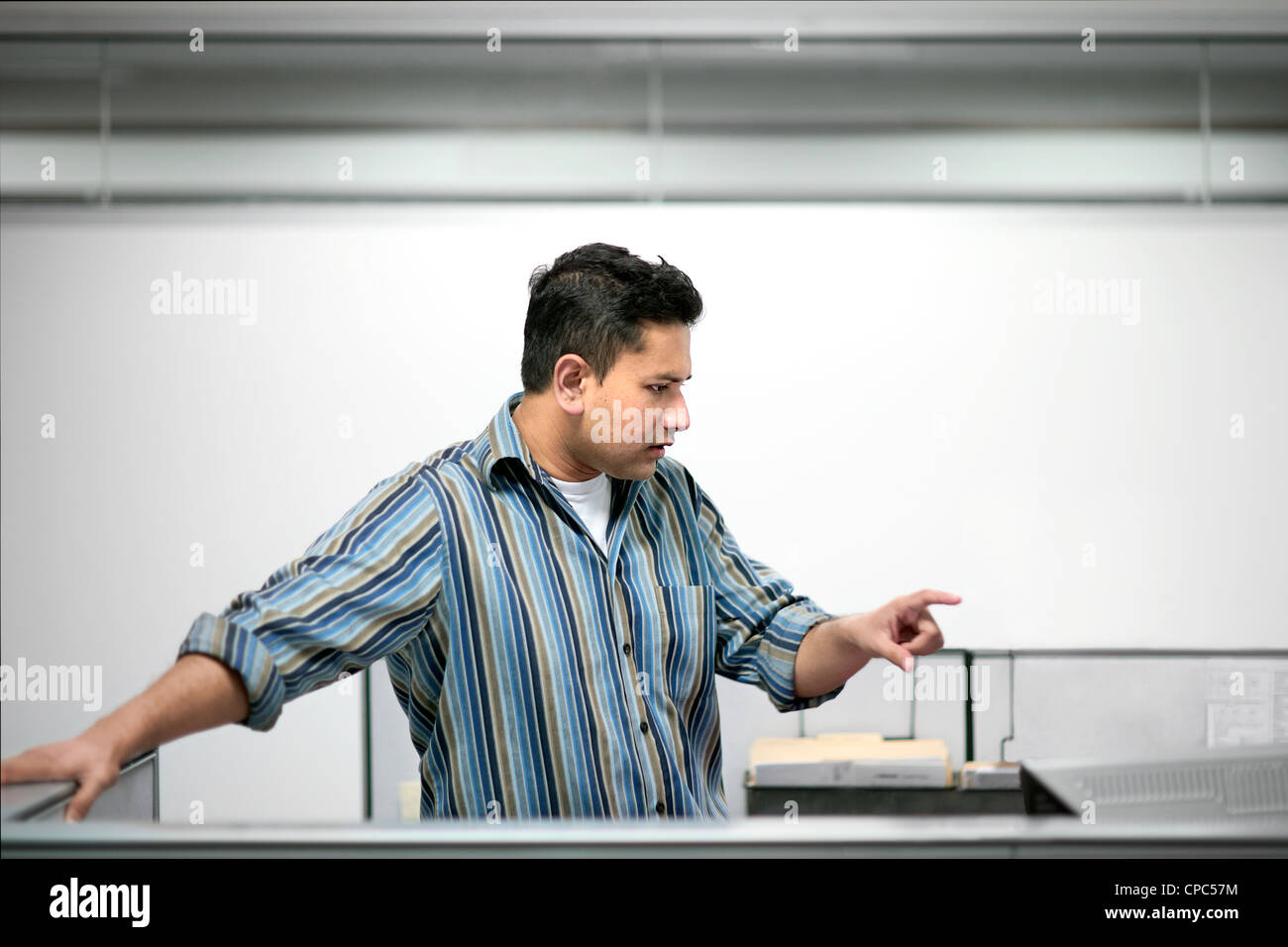 A worker points his finger while standing in a cubicle - Stock Image