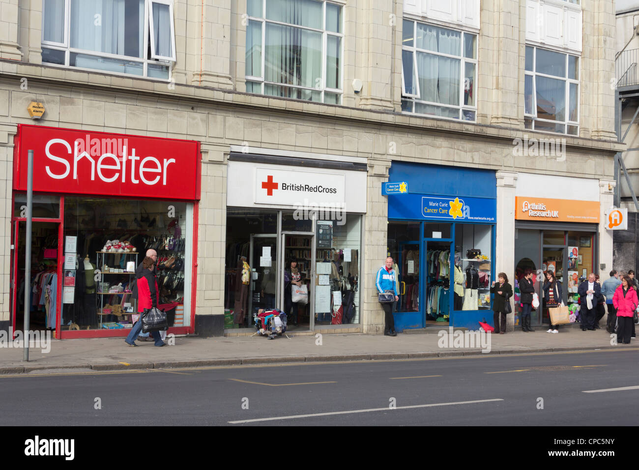 A row of four charity shops, Shelter, British Red Cross, Marie Curie and Arthiritis Research UK on Great Moor Street - Stock Image