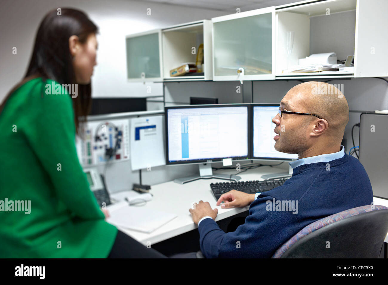 Two People talking at a cubicle in an office. - Stock Image