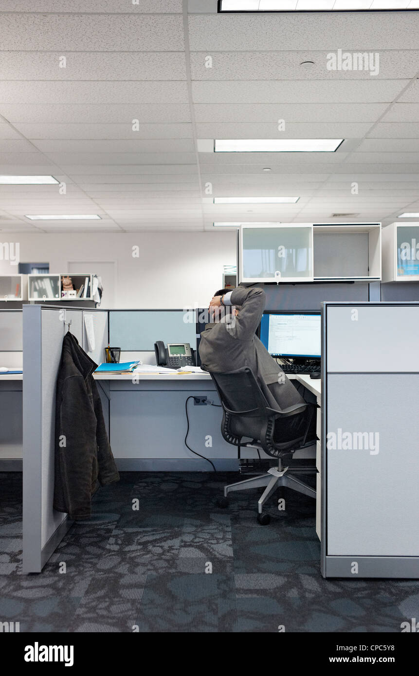 A man puts his hands behind his head while working in his cubicle - Stock Image