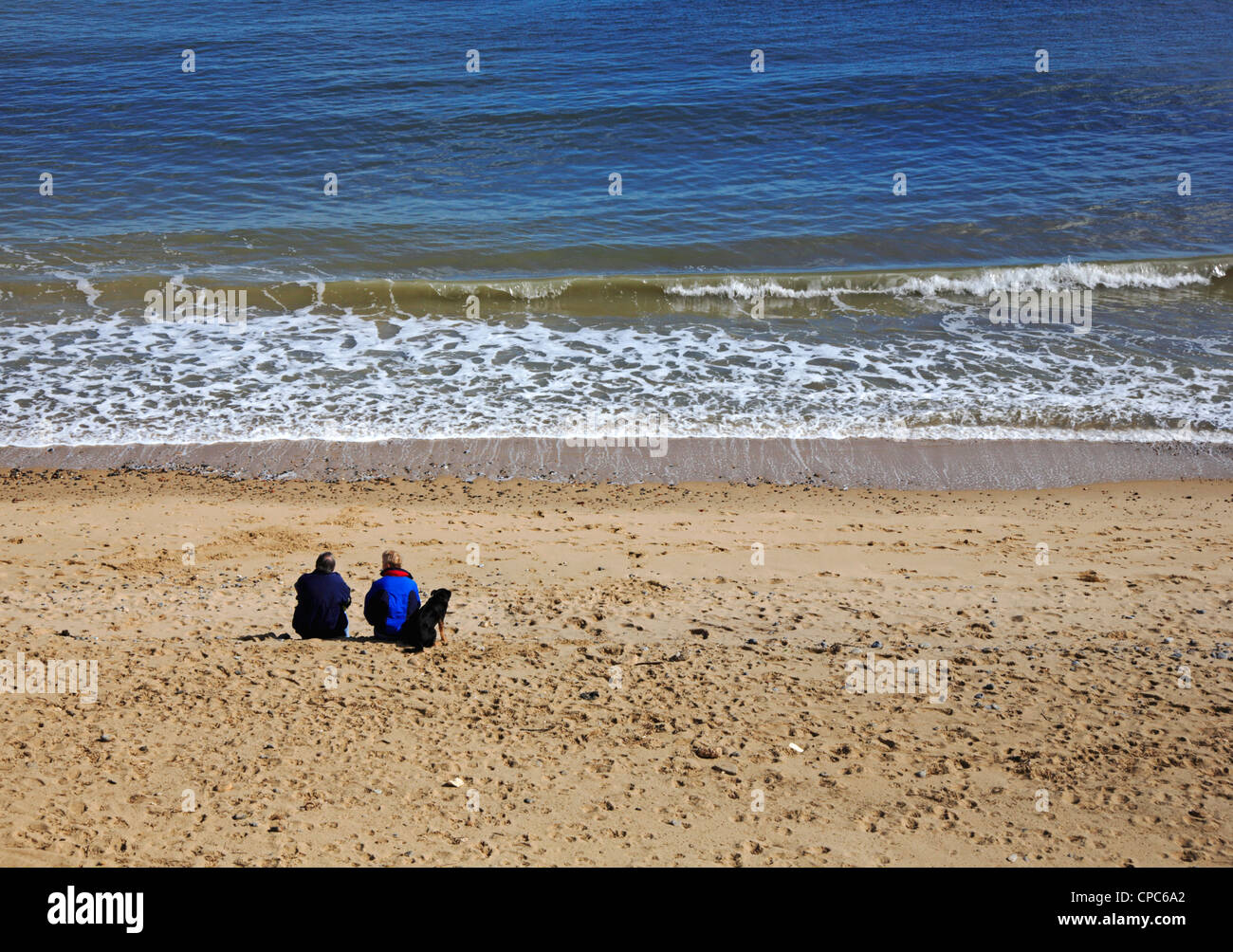 An elderly couple with their dog sitting on the beach and staring out to sea at Happisburgh, Norfolk, England, United Stock Photo