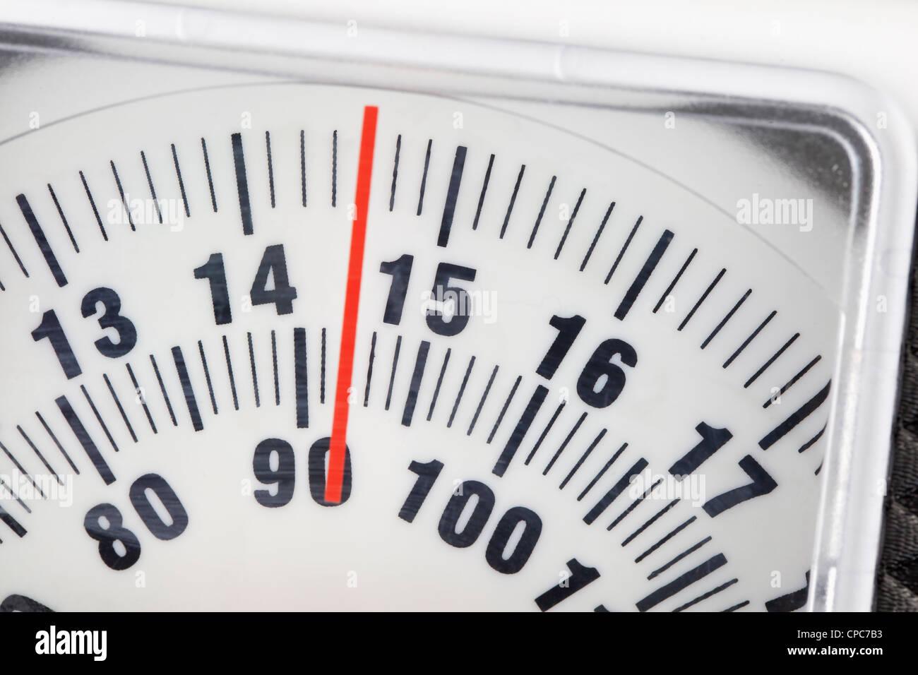 Bathroom scale indicating 92 kilograms - Stock Image