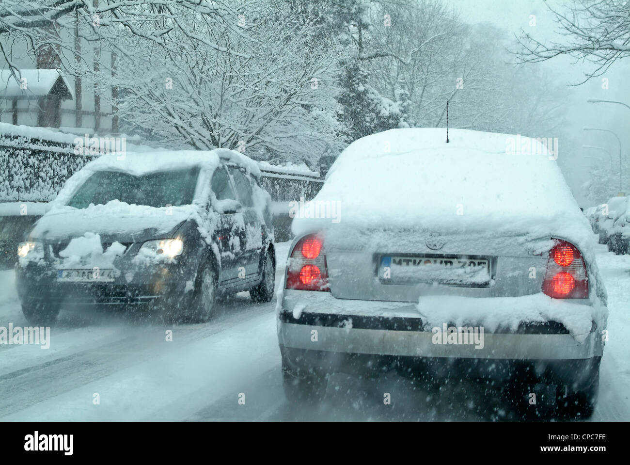 Snow covered cars on a winter road. - Stock Image