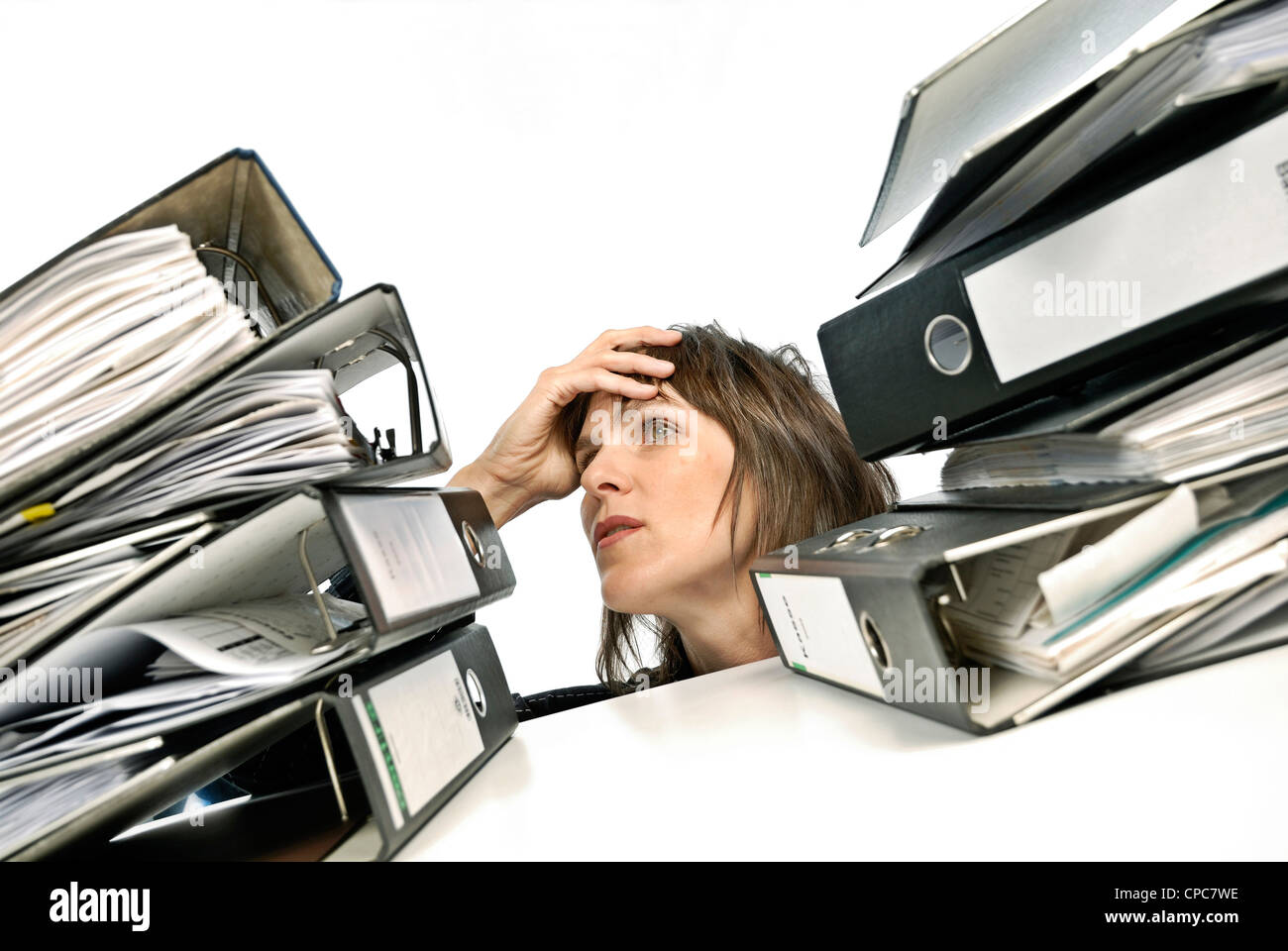 Overburdened staff between two stacks of files. - Stock Image