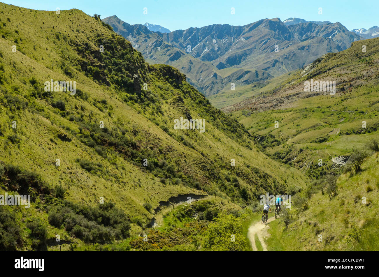 Mountain bikers descending the Pack Track, Skippers Canyon, near Queenstown, with Mt Aurum on the skyline, New Zealand - Stock Image