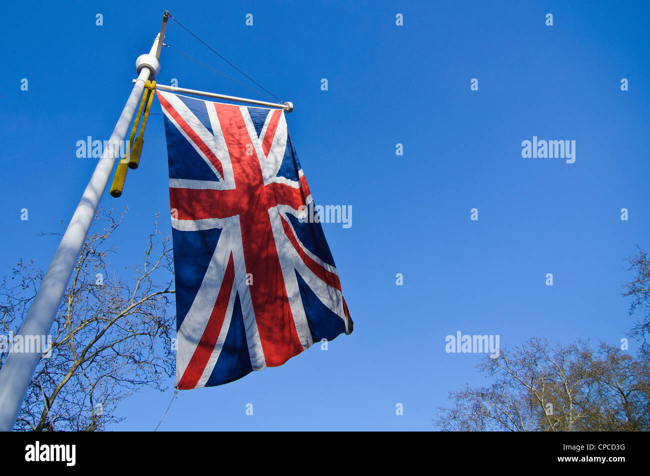 Union Jack flag against a blue sky in spring in London - Stock Image