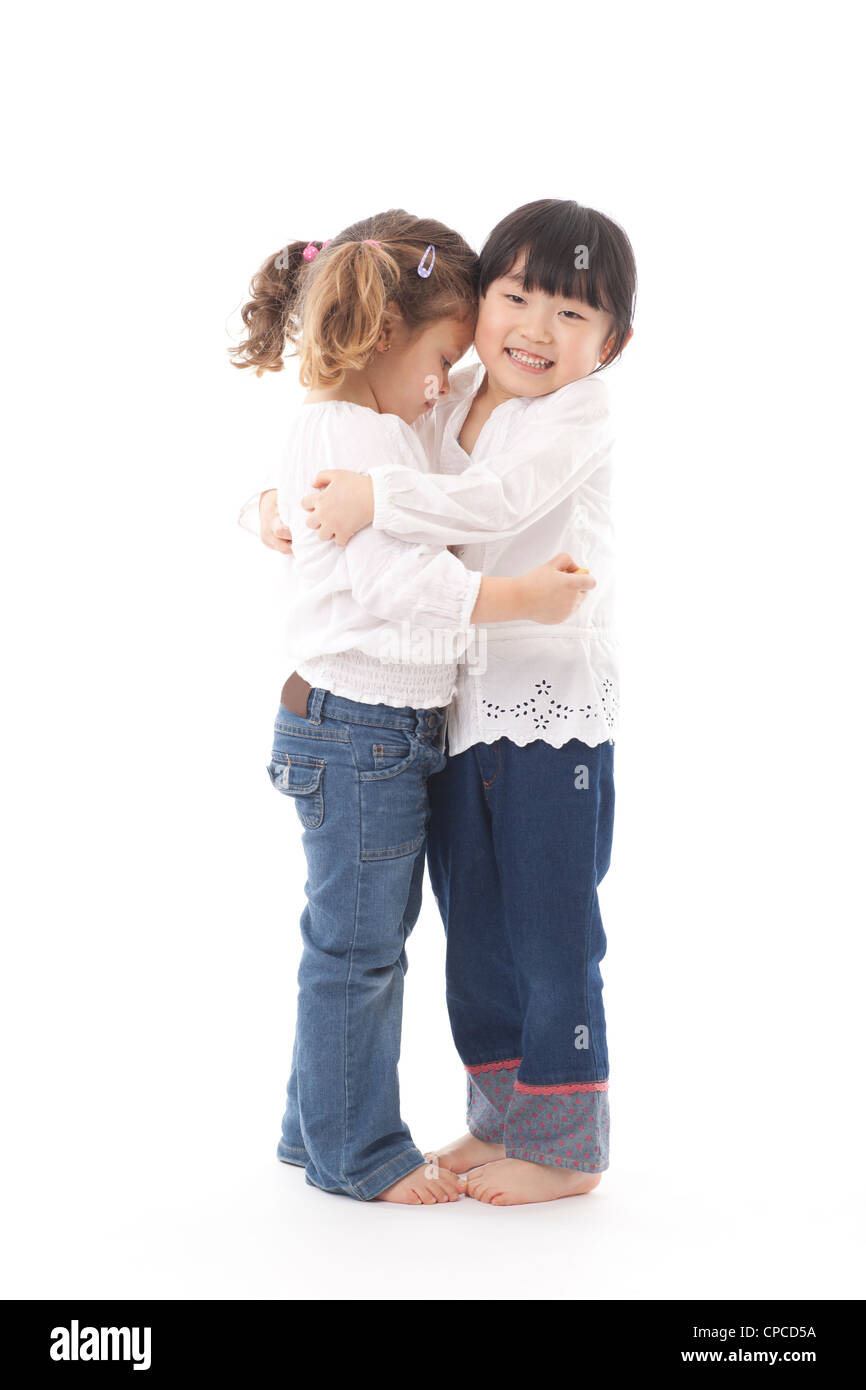 Two young girls hugging each other. Studio shot against a white background. - Stock Image