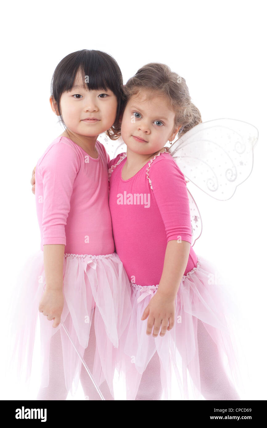 Two young girls wearing pink tutus shot in the studio against a white background. - Stock Image