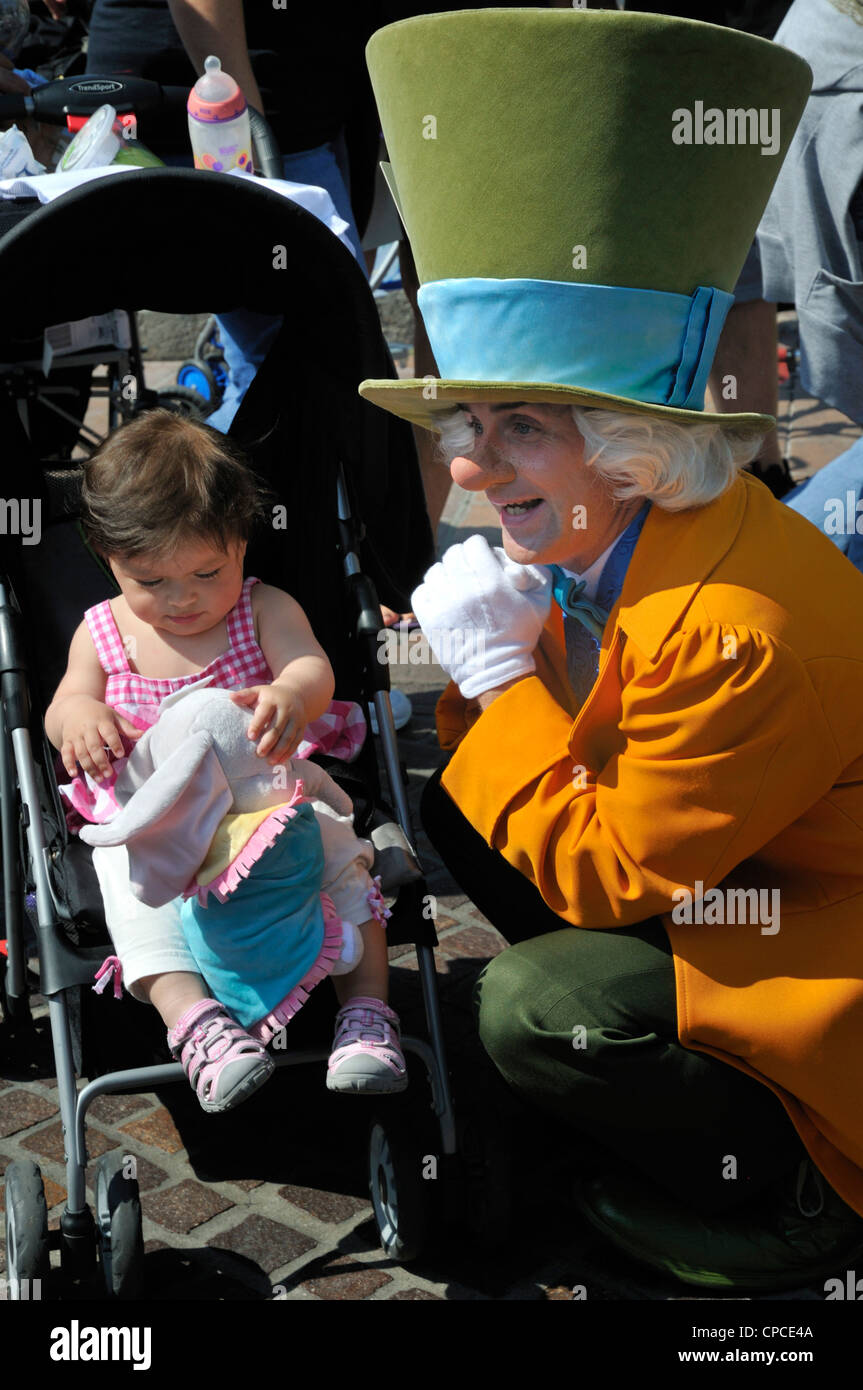 The Mad Hatter amuses a child at Anaheim Disneyland - Stock Image