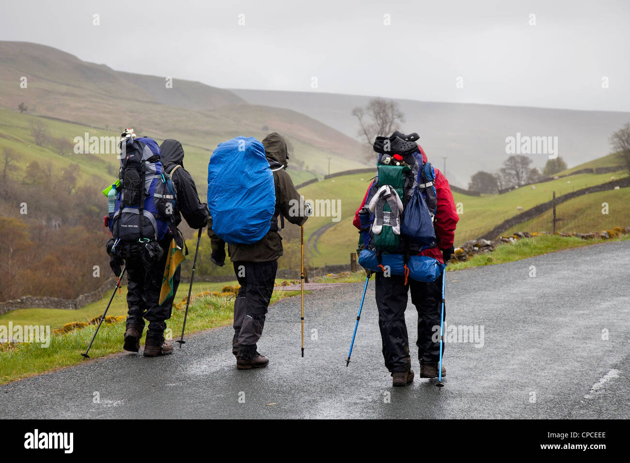 Three men; Coast to Coast walkers in Swaledale. Man on the route from Keld to Gunnerside, and Reeth, North Yorkshire - Stock Image