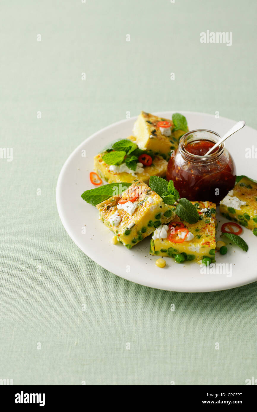 Plate of quiche with peas and tomatoes - Stock Image